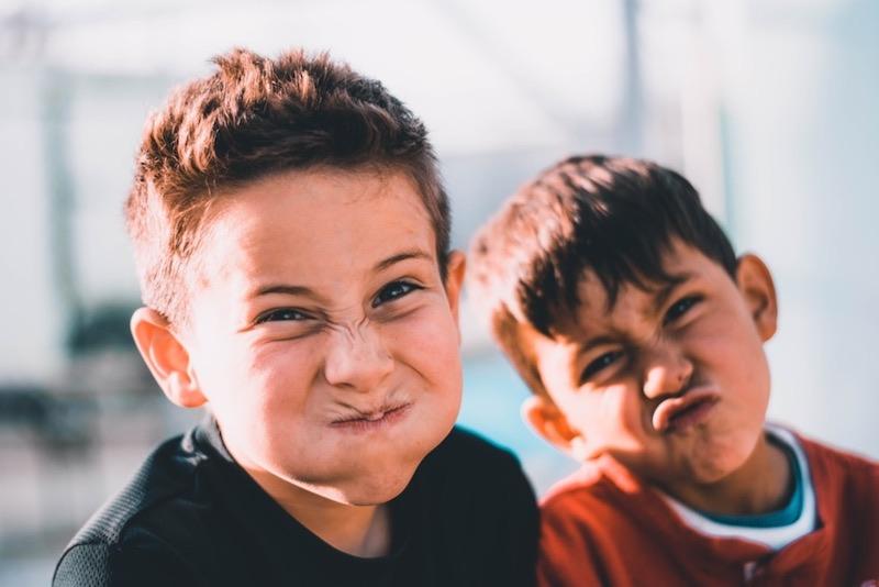 Dwóch uczniów robi śmieszne miny